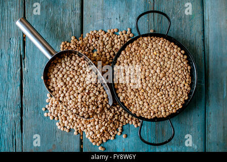 Skillet and metal scoop with dried brown lentils on wood - Stock Photo