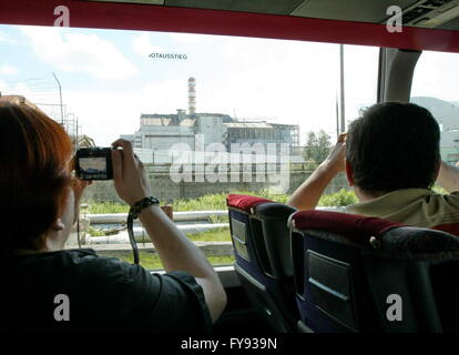 CHERNOBYL, UKRAINE. Pictured in this file image are people taking pictures of a sarcophagus covering Unit 4 of the - Stock Photo