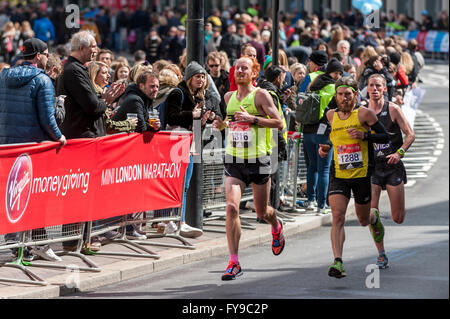 London, UK. 24 April 2016. Club runners take part in the Virgin Money London Marathon, passing through mile 23. - Stock Photo