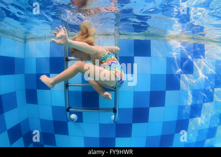Funny photo of baby girl swimming and diving in pool with fun - jumping deep down underwater with splashes and foam. - Stock Photo