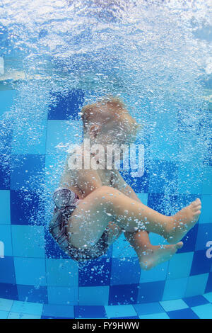 Funny photo of baby boy swimming and diving in pool with fun - jumping deep down underwater with splashes and foam. - Stock Photo