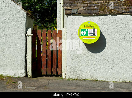 Defibrillator mounted in wall in village, England UK - Stock Photo
