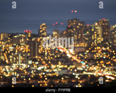 A bokeh view of Honoluu city lights at dusk from the Tantalus overlook. - Stock Photo