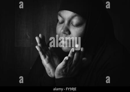 African muslim woman weiring a black veil in prayer - Stock Photo
