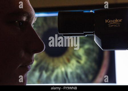 Optician looking at eye through microscope Pic Peter Devlin - Stock Photo