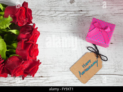 Happy Anniversary text with small gift box and red roses on white rustic wooden table. - Stock Photo