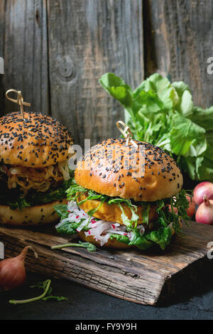 Two Homemade veggie burgers with sweet potato, fresh radish and pea sprouts, served on wooden chopping board over - Stock Photo