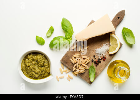 Fresh basil pesto ingredients on white background overhead shoot. - Stock Photo