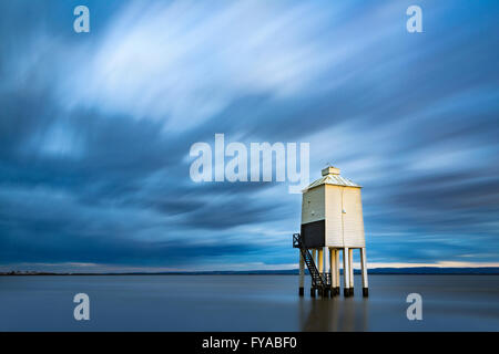 The low lighthouse at Burnham-on-sea is lit by a shaft of sunlight at sunset. A long exposure blurs the clouds and - Stock Photo