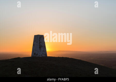 The sun rises behind a Triangulation Station or Trig Point on a clear morning. - Stock Photo