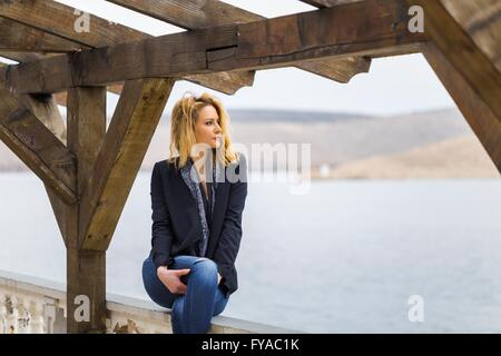 Daydreaming looking away young woman sitting on edge fence overlooking sea alone lonesome lonely sole single denims - Stock Photo