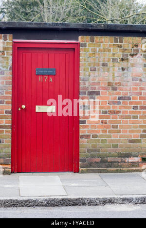 Red front door set in a wall garden entrance - Stock Photo