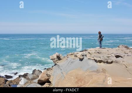 A woman standing alone on the rocky edge of a cliff at Salt Point State Park on the northern California coast. - Stock Photo