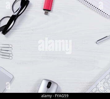 Top view of various office work objects forming circle pattern on white desktop. - Stock Photo
