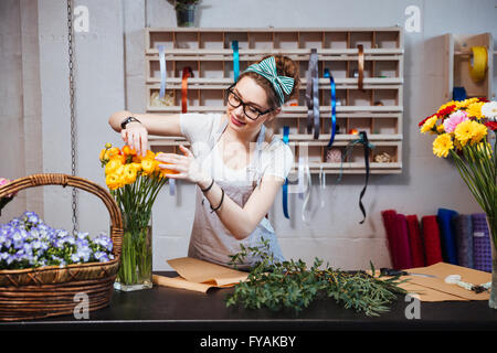 Smiling charming young woman florist taking care of yellow roses in flower shop - Stock Photo