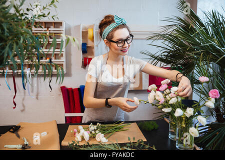 Smiling attractive young woman florist working and making bouquet in flower shop - Stock Photo