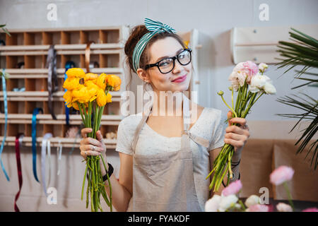 Happy beautiful young woman florist holding white and yellow flowers in shop - Stock Photo