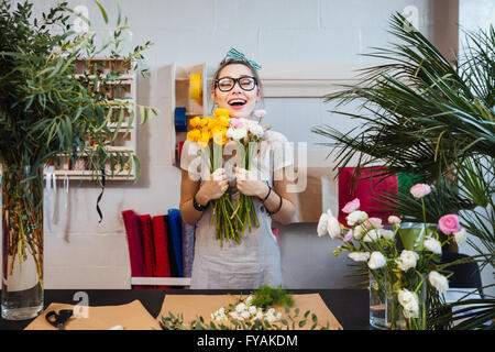Happy excited young woman florist with bunch of flowers standing and laughing in shop - Stock Photo
