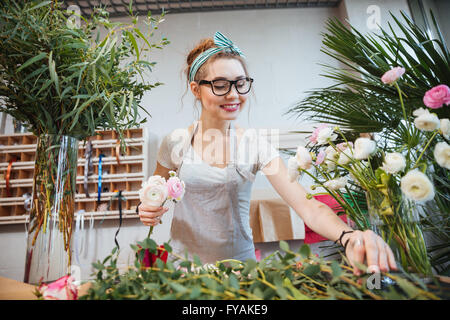 Happy lovely young woman florist making bouquet in flower shop - Stock Photo