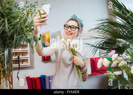 Happy pretty young woman florist taking selfie with smartphone in flower shop - Stock Photo