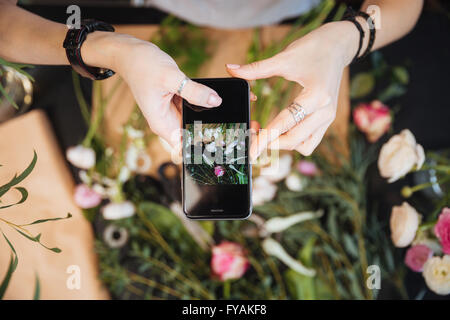 Top view of hands of woman florist taking pictures of flowers with mobile phone - Stock Photo