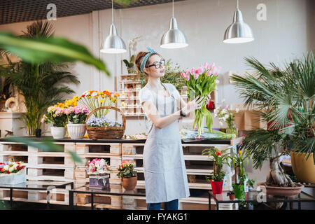 Beautiful young woman florist in glasses standing and holding bunch of pink tulips in flower shop - Stock Photo