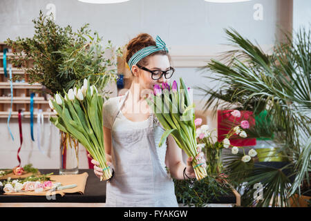 Happy lovely young woman florist holding and smelling tulips in flower shop - Stock Photo