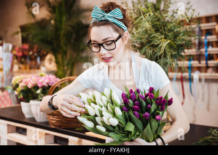 Cute lovely young woman florist in glasses taking care of tulips in flower shop - Stock Photo