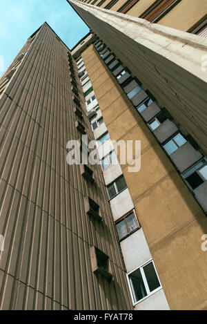 Socialist architecture example, tall residential skyscraper building, low angle view, retro toned - Stock Photo
