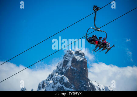 A group of skiers on a chairlift in front of L'aiguille du Fruit in the ski resort of Courchevel in the French Alps. - Stock Photo
