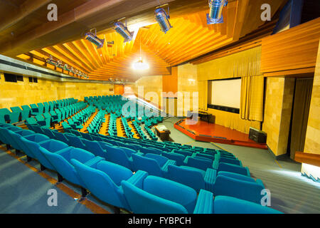View from stairs on screen and rows of comfortable chairs in cinema hall - Stock Photo