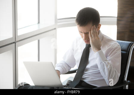 Handsome young stressed businessman sitting in his office using laptop. Caucasian businessperson holding his head - Stock Photo