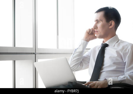 Portrait of serious handsome young business man working on laptop computer and making call. Caucasian businessperson - Stock Photo