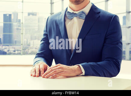 close up of man in suit and bow-tie at table - Stock Photo