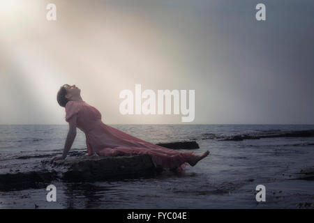 a woman in a pink dress is lying on stones at the sea - Stock Photo