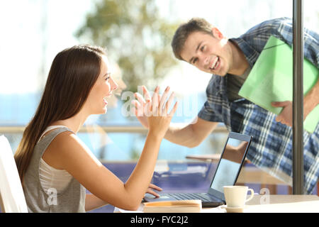 Happy friends or couple greeting waving hands and looking each other in a date in a coffee shop - Stock Photo