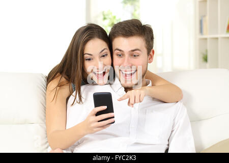 Attractive surprised and amazed couple watching smart phone together sitting on a couch in a living room at home - Stock Photo