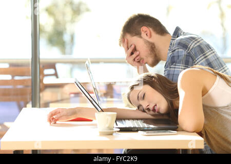 Side view of tired students surrendering to fatigue studying with laptops in a coffee shop with a window in the - Stock Photo