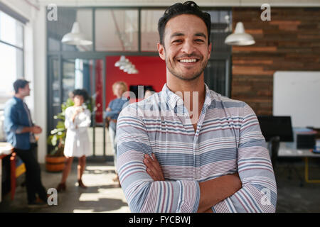 Portrait of a handsome young business man standing with arms crossed in an office. Smart caucasian young male designer - Stock Photo
