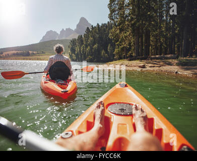 Couple canoeing in the lake on a summer day. Man and woman in two different kayaks in the lake on a sunny day. - Stock Photo