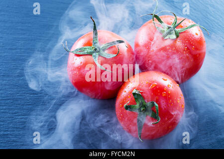 tomatoes in smoke on a slate table. - Stock Photo