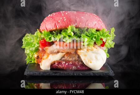 big red hamburger with smoke on a slate table. - Stock Photo