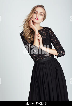 Beautiful young woman in dress posing on gray background. - Stock Photo