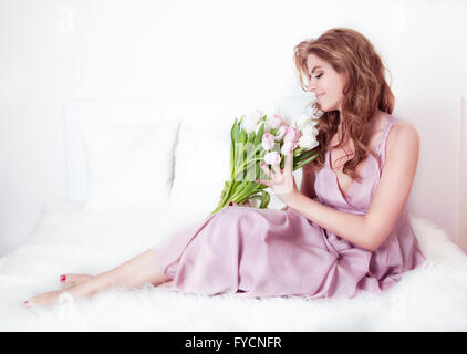 Beautiful woman with a bouquet of flowers, sitting in the room. The gentle tone. - Stock Photo