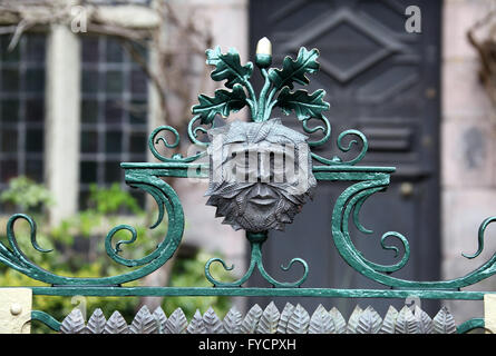 The gate of 17th century Greystones House in Leek with a decorative Green Man face. - Stock Photo