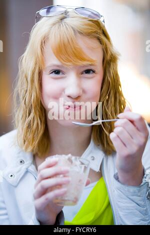 Teen girl portrait eating eat spoon smile smiling happy full mouth mouthful eating icecream ice-cream cream from - Stock Photo