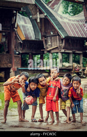 Traditional Torajan Tongkonan houses with a gang of young indigenous kids posing for a candid photo - Stock Photo