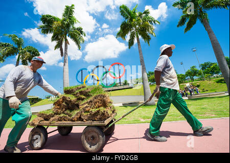 RIO DE JANEIRO - MARCH 18, 2016: Maintenance workers transport landscaping materials in front of Olympic Rings. - Stock Photo