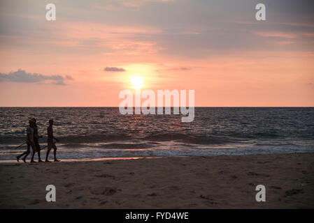 Fishermen walking at the Weligama beach in southern province of Sri Lanka at the time of sunset. - Stock Photo