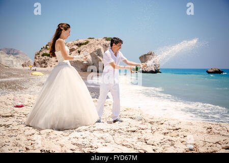 bride and groom open champagne on the beach Mediterranean Sea - Stock Photo